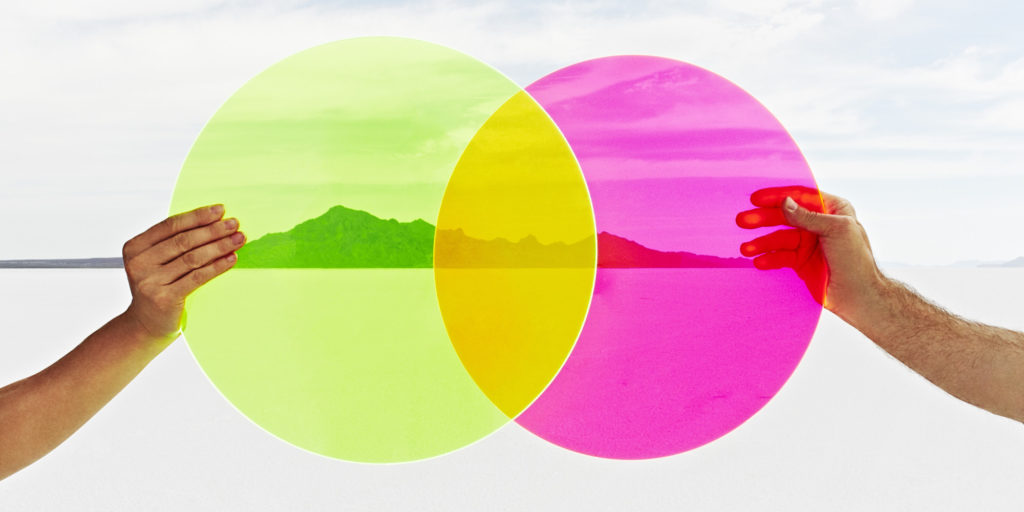 Two hands holding colored circles in landscape.